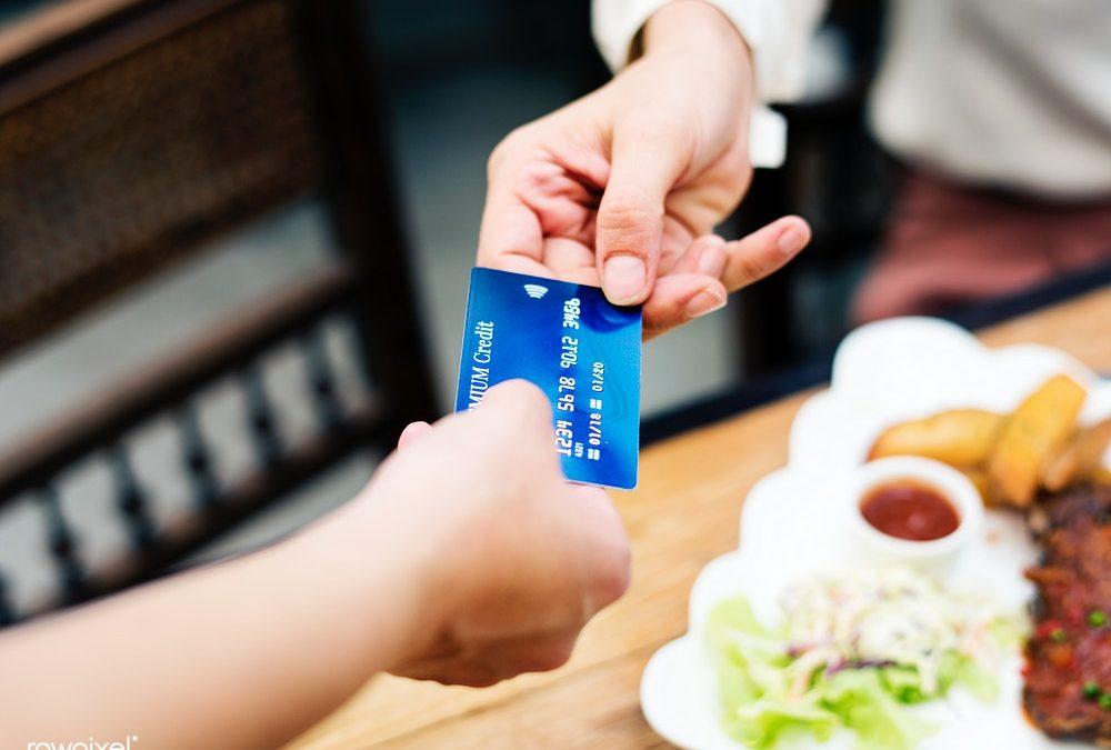 Mulher entregando seu cartão de crédito para o atendente